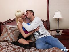 Mini-skirt clad blonde with big tits enjoying a hardcore fuck on her bed