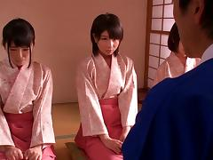 Three Asian bitches wearing kimonos play with a guy's dick indoors