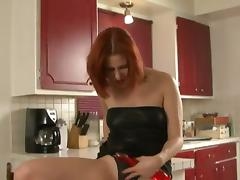 Alluring redhead solo model in thong drilling her pussy using toy in the kitchen
