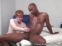 Tattooed gay guy with short red hair playing with a big black cock