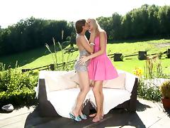 Girls in dresses kiss passionately outdoors before lesbian sex