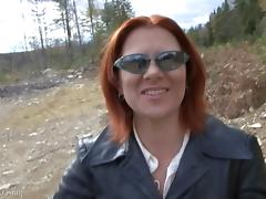 Mature redhead called Mina smokes a cigarette outdoors