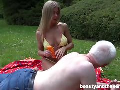 Grandpa lotions up and fucks a bikini girl in the grass