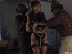 Fishnet-clad Asian sex slave with a hot ass sucking a stranger's cock