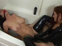 Lesbians in latex play with dildo in bathtub
