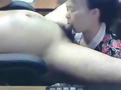 Ponytailed asian girl gives her man a blowjob, while he sits on an office chair.