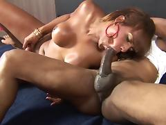 Oiled-up Latin tranny with amazing juggs and a tight hot ass sucking a big black cock