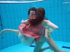Two saucy lassies remove their clothes under the water