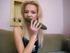 Teen beauty plays with a cucumber