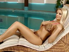 Stunning blonde chick finger fucks her pussy lying on the lounge